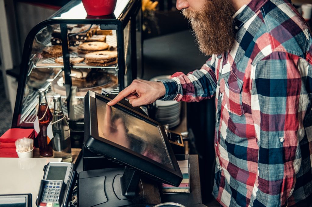 A man at the counter using cash register in a coffee shop.
